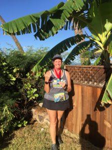 Linda Jerome models her half marathon finisher medal at the 2018 Maui Marathon!